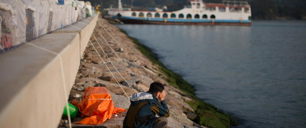 Image: A man sits beside the sea near an area where relatives of missing passengers from the Sewol ferry are gathered at Jindo harbor on April 23, 2014.