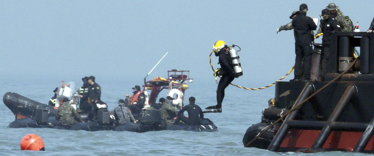 Image: A diver jumps into the sea to look for people trapped in the sunken Sewol ferr