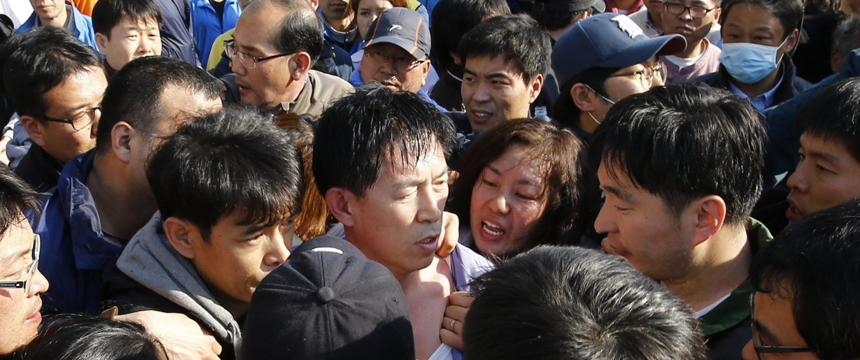 Image: Angry family members of passengers on capsized South Korean ferry demand officials for faster and more efficient rescue work in Jindo