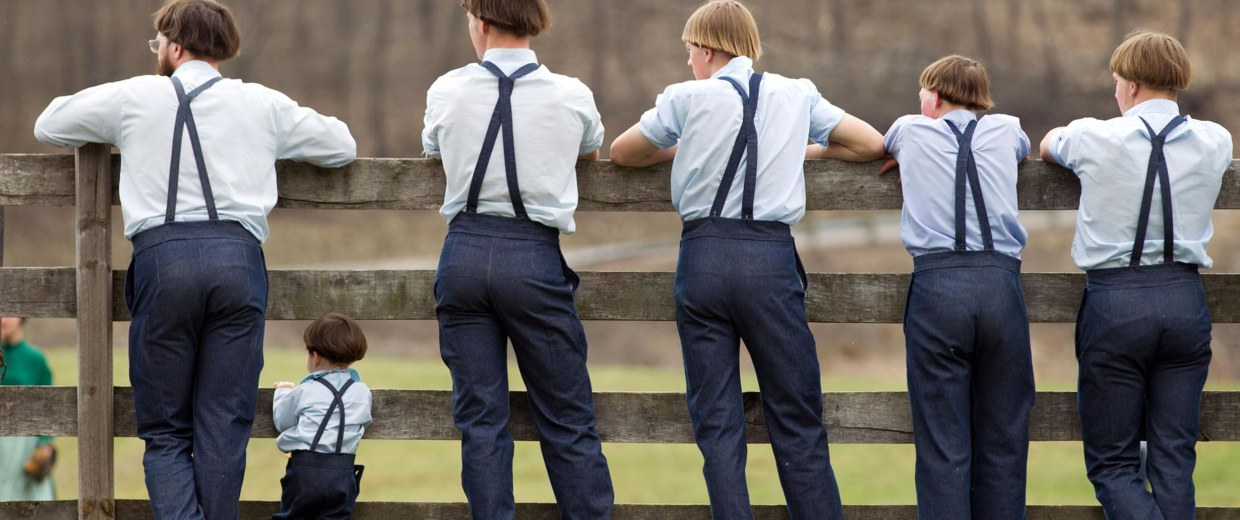 Image: Amish boys watch a game of baseball outside the school
