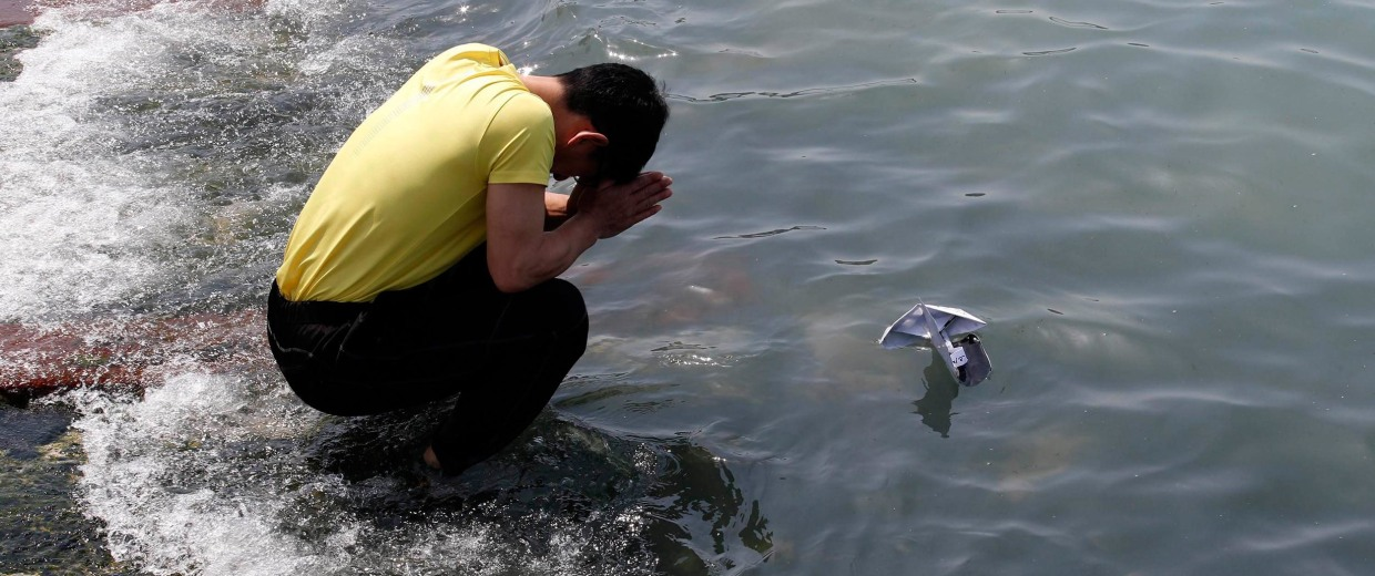 Image: Family member of a victim onboard capsized Sewol ferry, prays for missing and dead passengers, as he releases a paper boat with a message for them, at a port in Jindo