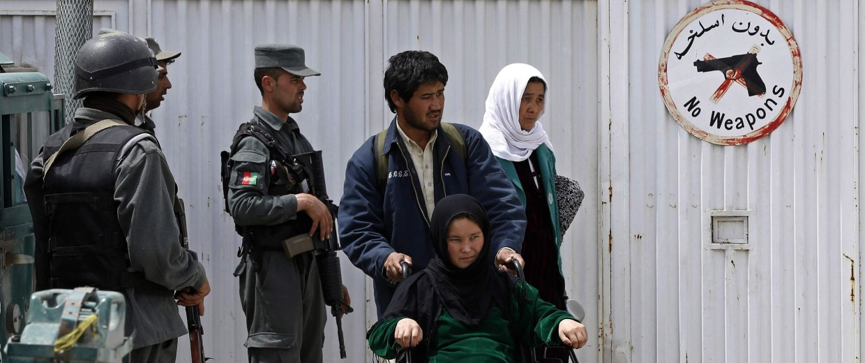 Image: A patient in a wheelchair is helped by relatives at the gate of Kabul's CURE Hospital after three Americans were killed