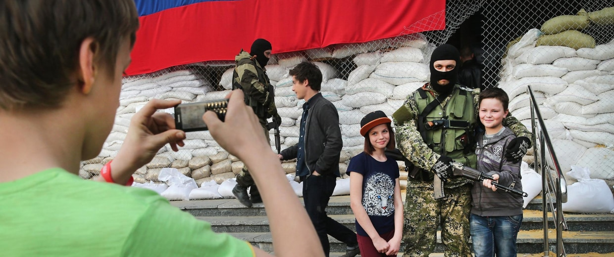 Image: A 12-year-old boy and girl pose for a picture with pro-Russian militant while their 14-year-old friend takes a picture outside the city council building in Slaviansk