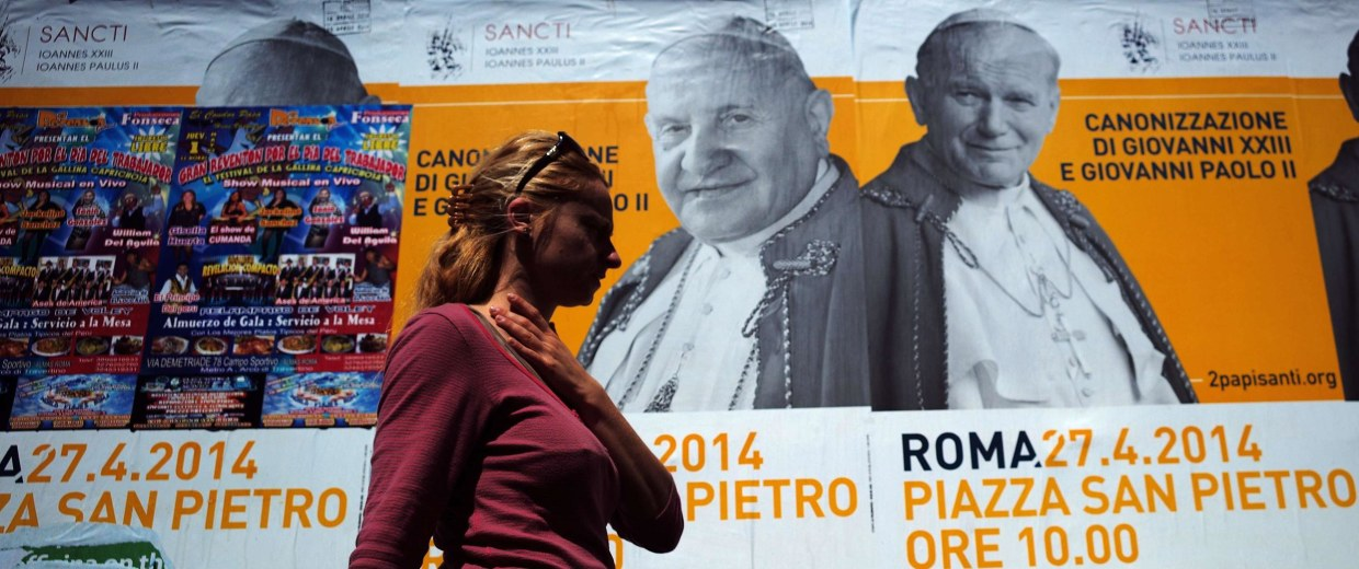 Image: A woman walks past posters announcing the double canonisation of Popes John Paul II and John XXIII