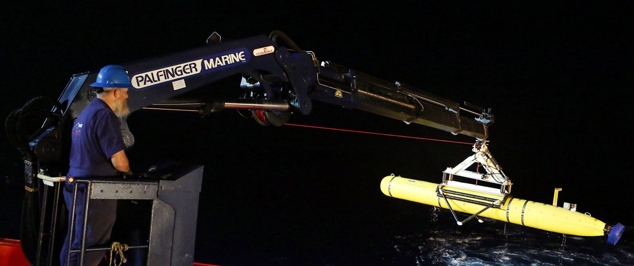 Image: Evan Tanner uses a crane to lift the Phoenix International AUV Artemis, also known as the Bluefin-21, back onto the Australian Defence Vessel Ocean Shield after searching for missing Malaysia Airlines Flight MH370, in Southern Indian Ocean