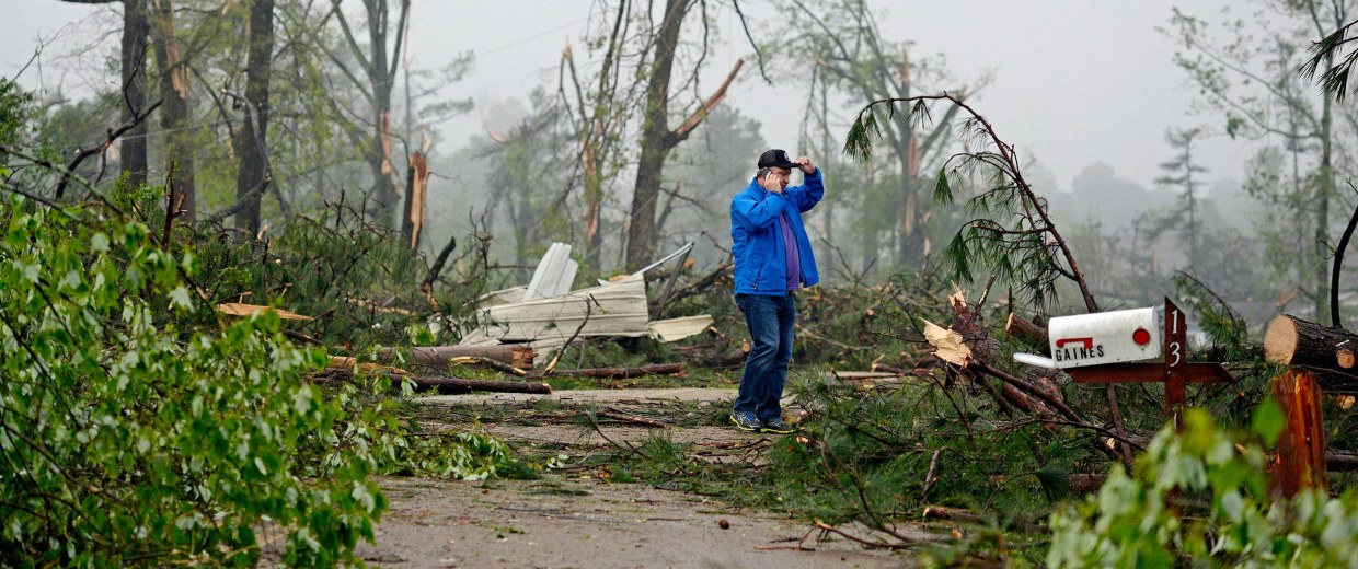 Image: Jeff Rogers talks on the phone while surveying damage around his home on Joyner Street in Tupelo, Miss.
