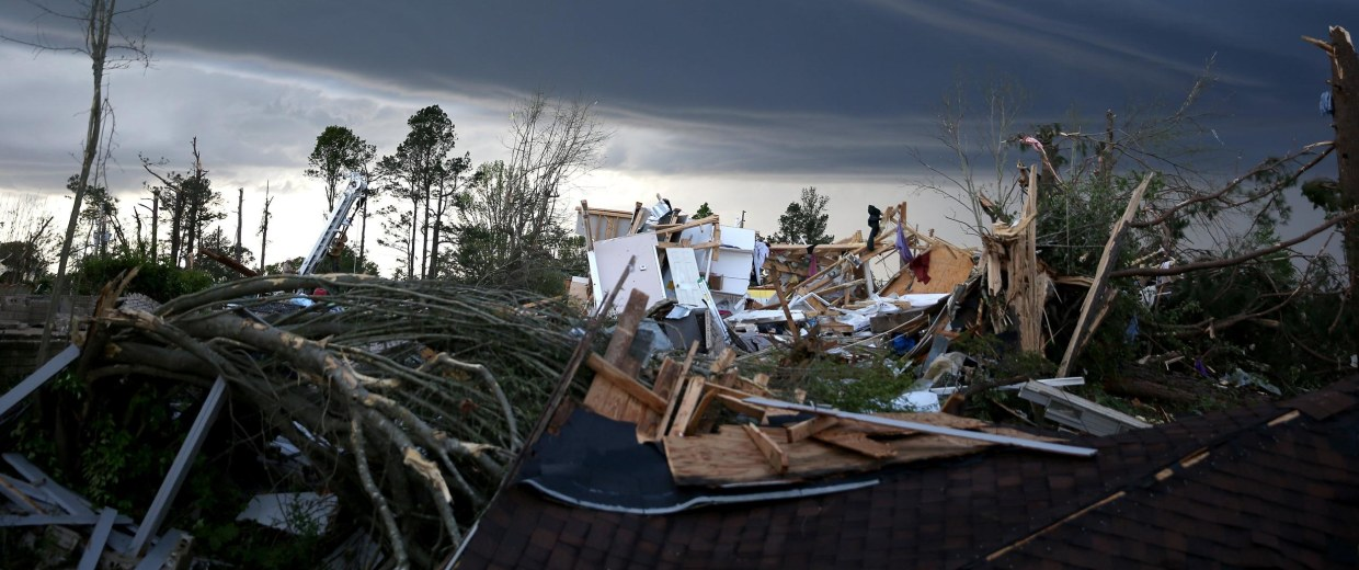 Image: An ominous cloud hangs above the remains of a home that was destroyed by a tornado in Tupelo, Mississippi.