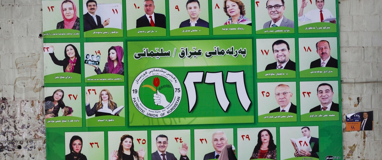 Image: A woman walks past a PUK campaign poster for Iraq's parliamentary elections in Sulaimaniya