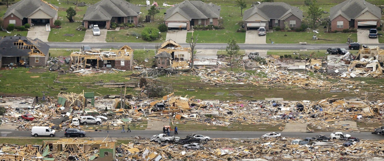Image: A row of lightly damages houses, top, face destroyed homes in a Vilonia, Ark., neighborhood Monday