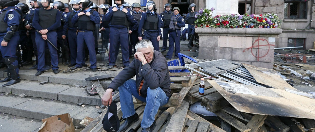 Image: A man reacts outside trade union building, where a deadly fire occurred, in Odessa.