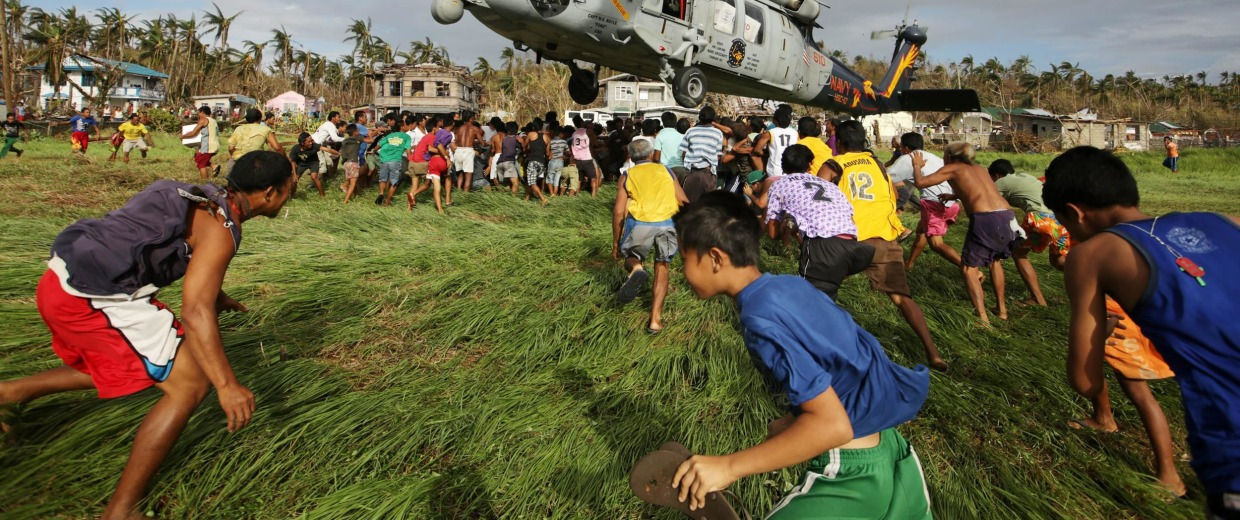Image: Filipino typhoon victims rush to get relief goods from a US Navy Sea Hawk helicopter