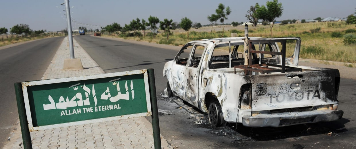 A burnt police patrol pick-up truck remains abandoned on the side of a deserted road in Damaturu, in the Yobe State