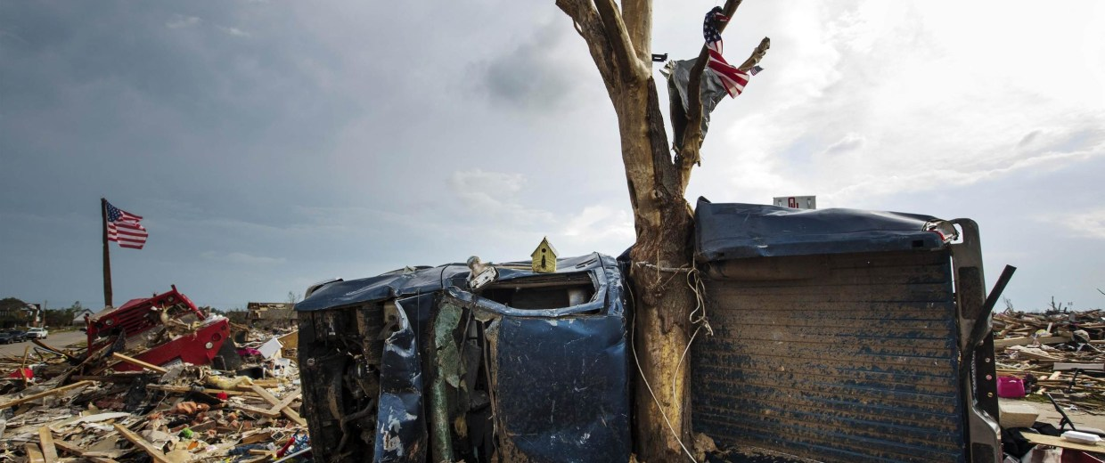 Image: File photo of a pickup truck is wrapped around a tree trunk after being thrown there by by a tornado in Moore Oklahoma