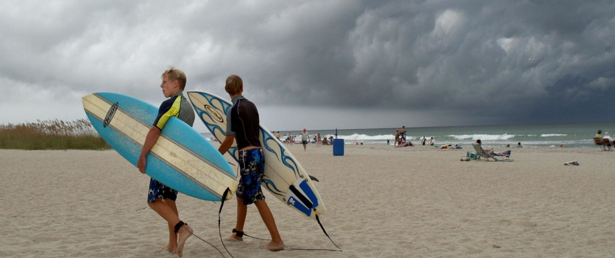 Image: Surfers leave the water under heavy clouds