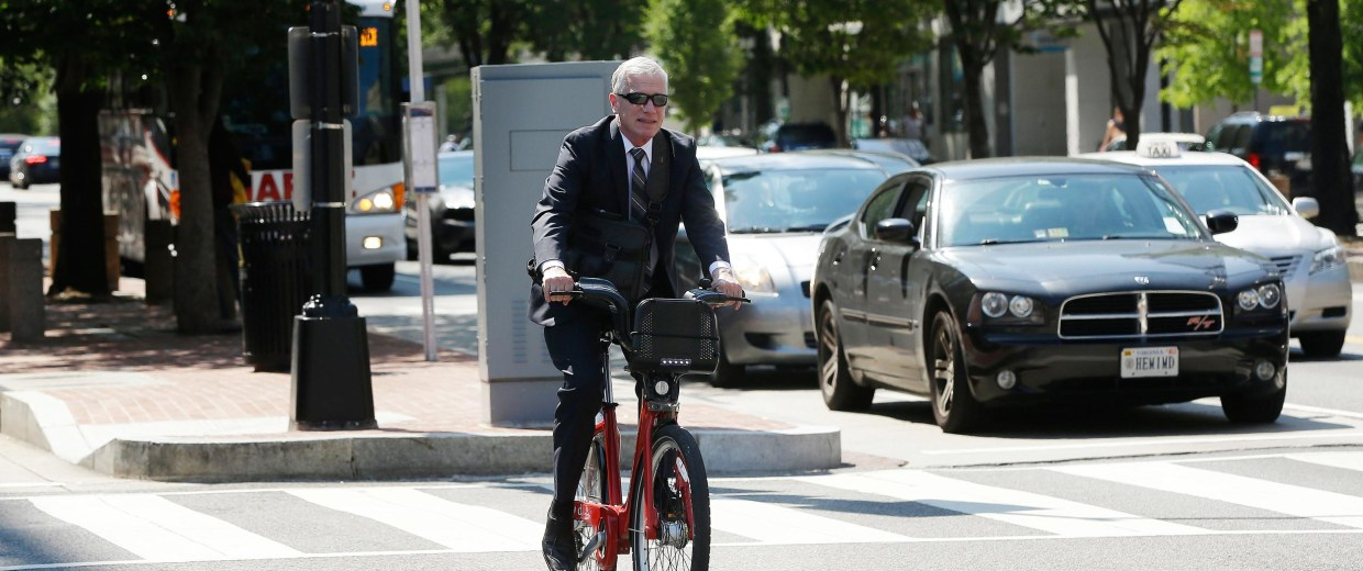 Image: A man wearing suit uses a Capital Bikeshare (CaBi) during rush hour in downtown Washington