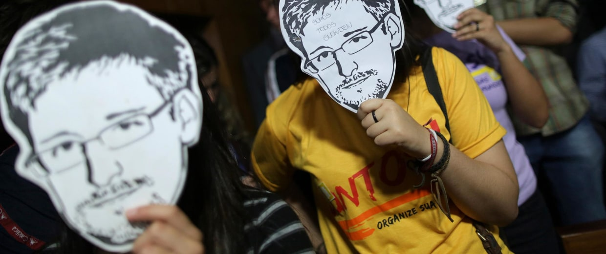 Image: People wear masks with pictures of Edward Snowden