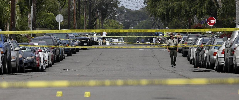 Image:  Santa Barbara County deputy sheriff walks along the street near the scene of a shooting on May 24, in Isla Vista, Calif.