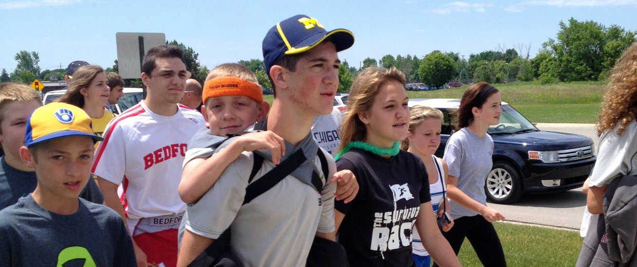 "Image: Hunter Gandee, 14, walks in Saline, Mich., on Sunday, June 8, 2014, during the second day of his two-day, 40-mile ""Cerebral Palsy Swagger"" walk"