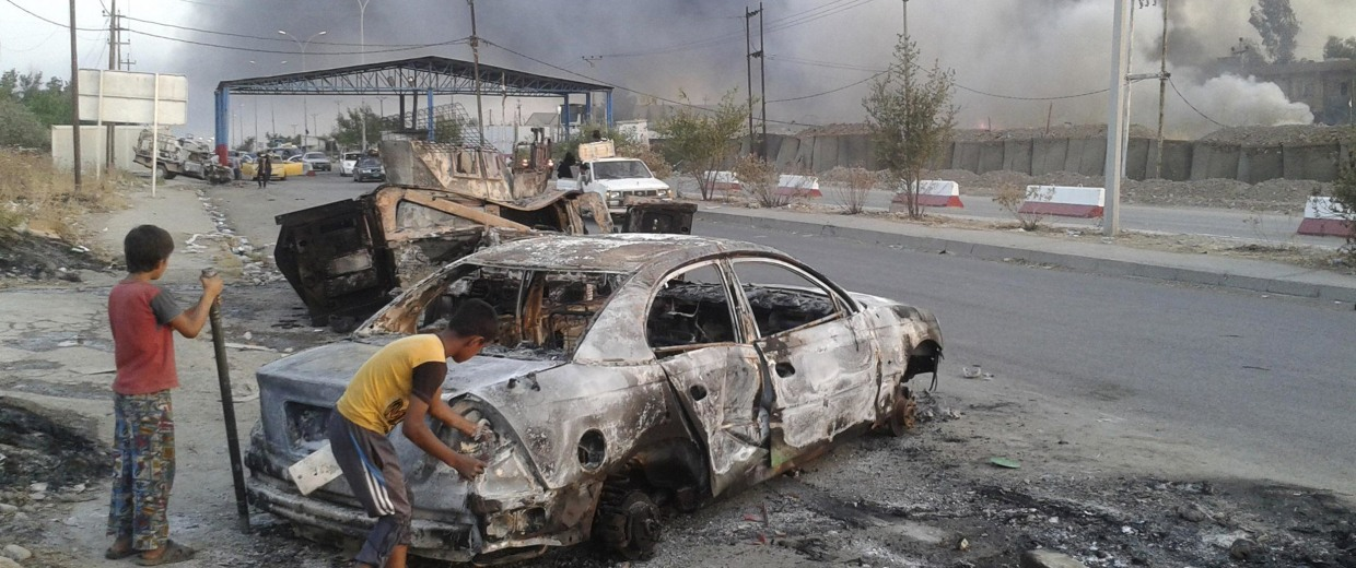 Image: Civilian children stand next to a burnt vehicle during clashes between Iraqi security forces and al Qaeda-linked ISIL in Mosul on June 10.