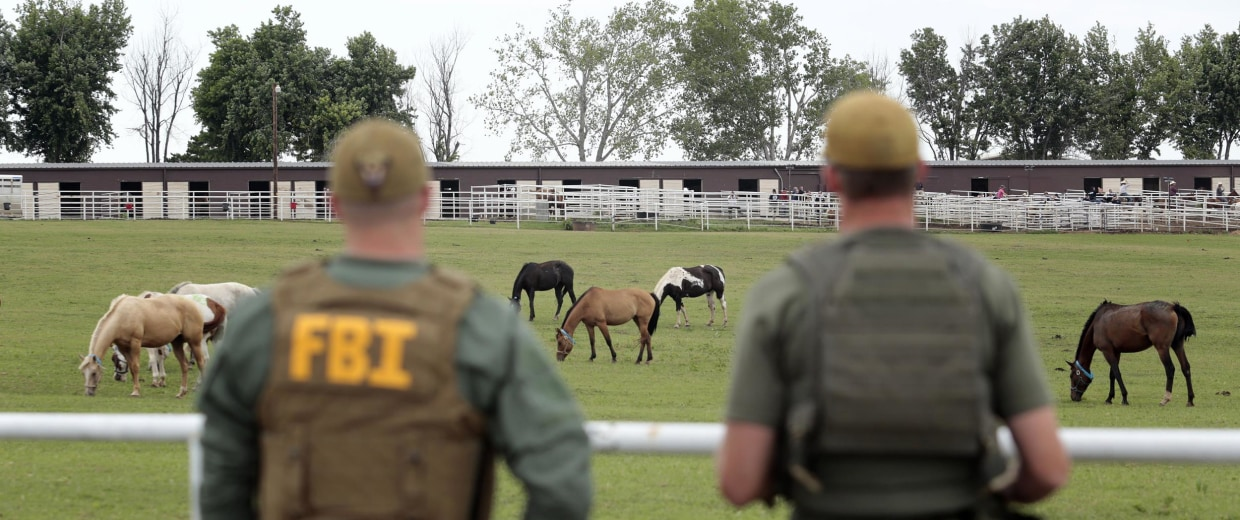 FBI agents overlook a horse ranch under investigation in Lexington, Okla.