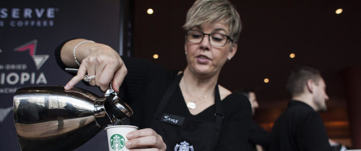 Image: Barista Sandy Roberts pours samples of Starbucks coffee during the company's annual shareholders meeting in Seattle