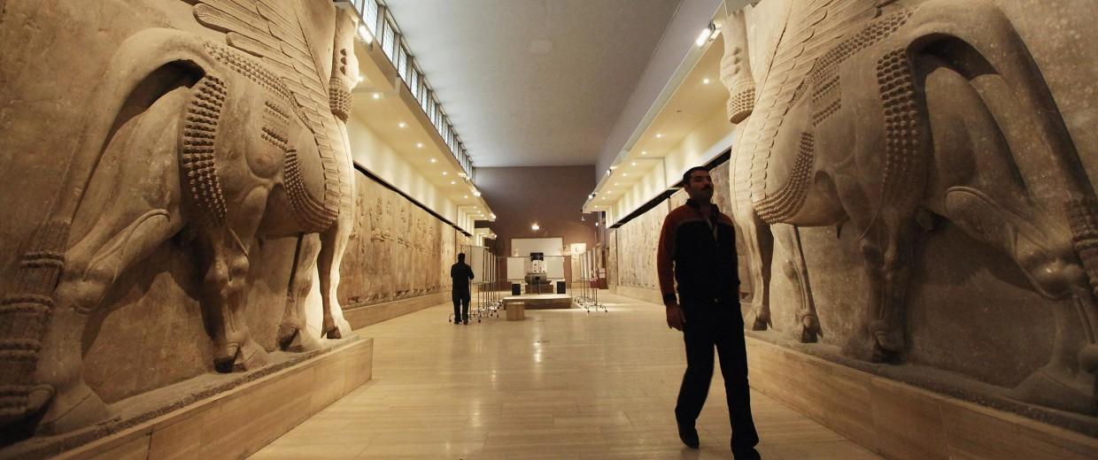 Image: A worker walks past sculptures at Iraq's National Museum in 2011.