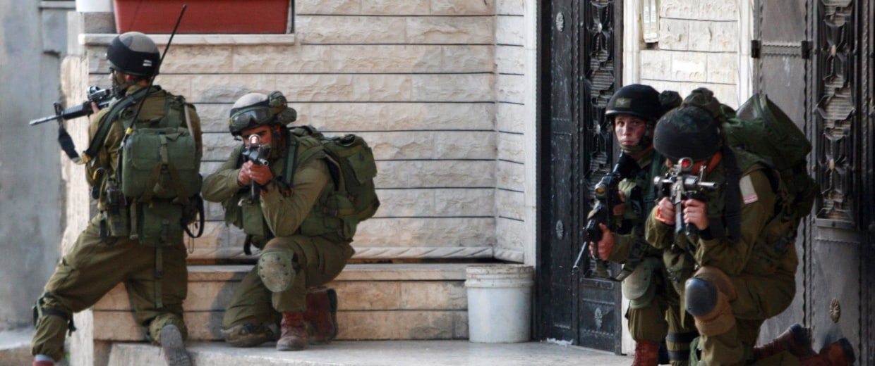 Image: Israeli army soldiers take up positions during a search operation in the West Bank