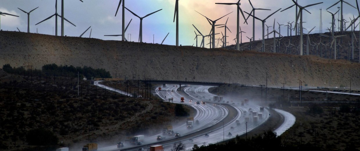 Image:  A rainbow forms behind giant windmills near rain-soaked Interstate 10 as an El Nino-influenced storm passes over the state
