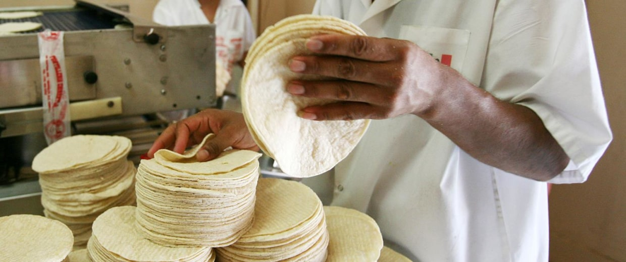 Image: A restaurant employee stacks corn tortillas.