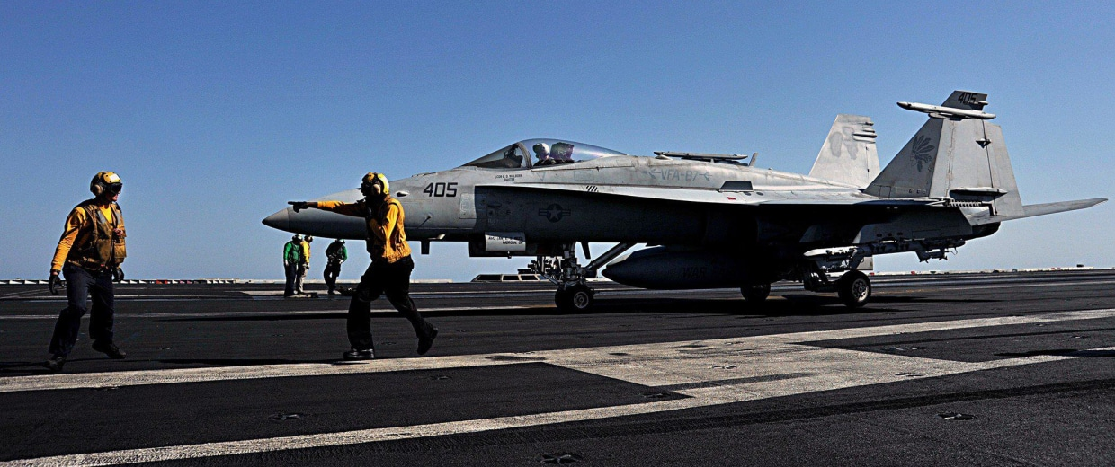 Image: Sailors direct an F/A-18C Hornet on the flight deck of the aircraft carrier USS George H.W. Bush