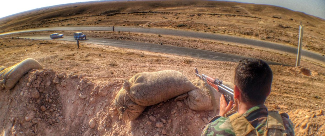 Image: A Kurdish Peshmerga trains his rifle on a suspicious car coming out Saadiyah