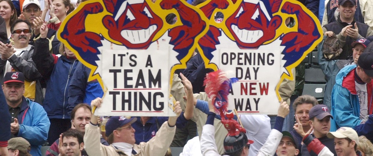 Image: Fans hold up Chief Wahoo logo signs as they celebrate the Cleveland Indians' opening win over the Minnesota Twins in Cleveland, Ohio