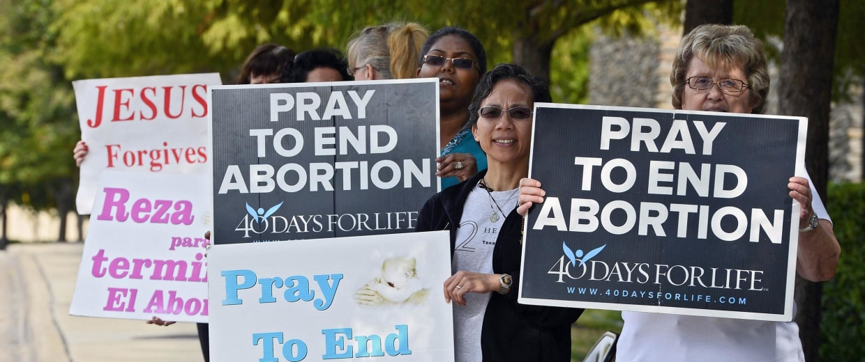 Image: Protesters stand with signs along the street in front of Southwestern Women's Surgery Center in Dallas, Texas, in 2013.