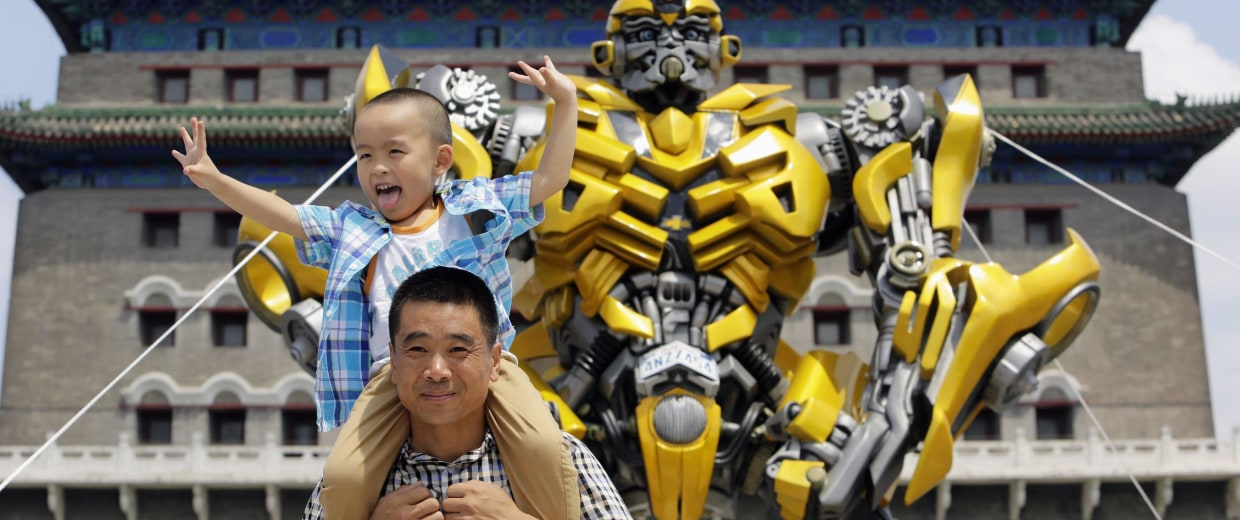 Image: A boy and his father pose for a photo next to a model of the Transformers character Bumblebee in central Beijing