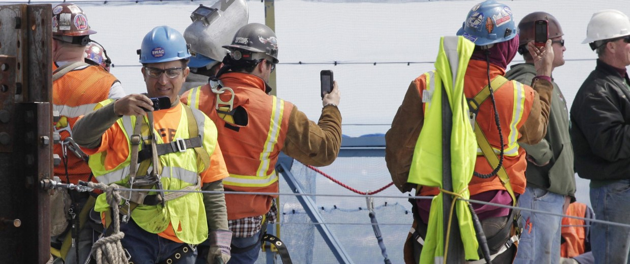 Image: Ironworkers use cell phones to take photos at One World Trade Center on April 30, 2012 in New York City.