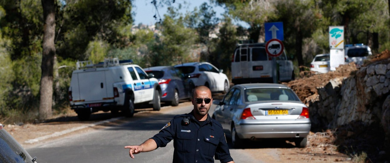 Image: An Israeli police officer gestures in the Jerusalem Forest