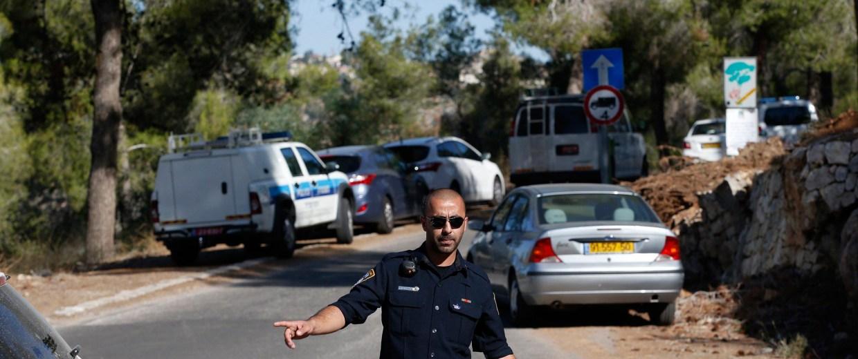 Image: An Israeli police officer gestures in the Jerusalem Forest