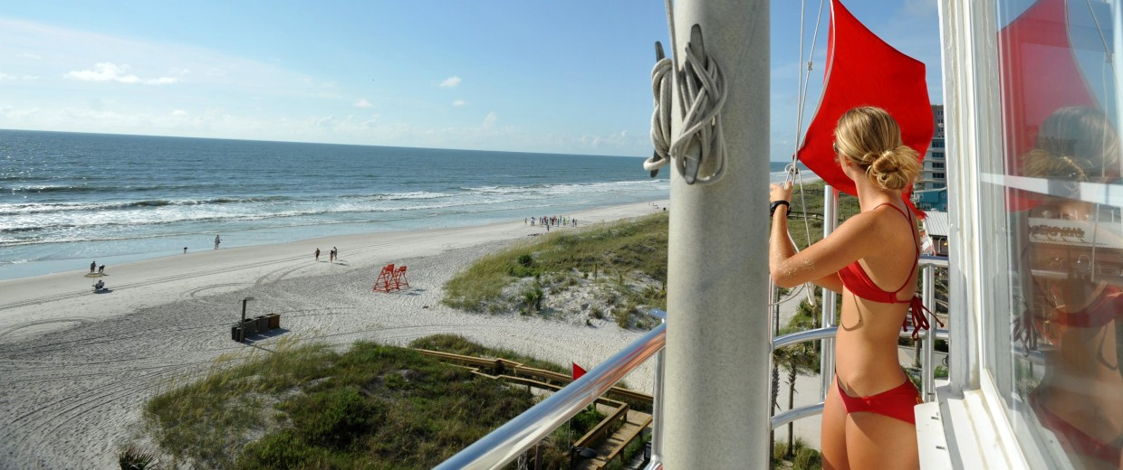 Image: Lifeguard Gabrielle Porter raises a red flag at the Red Cross lifeguard station in Jacksonville Beach, Fla., signaling a high risk of rip currents and high waves.