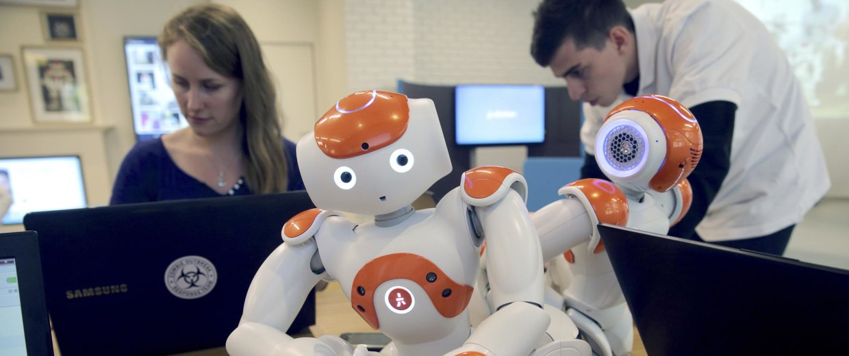 "Image: Visitors and staff work on computers next to humanoid robots ""Nao"" at the workshop of Aldebaran Robotics company during its opening week in Issy-Les-Moulineaux near Paris on July 2"