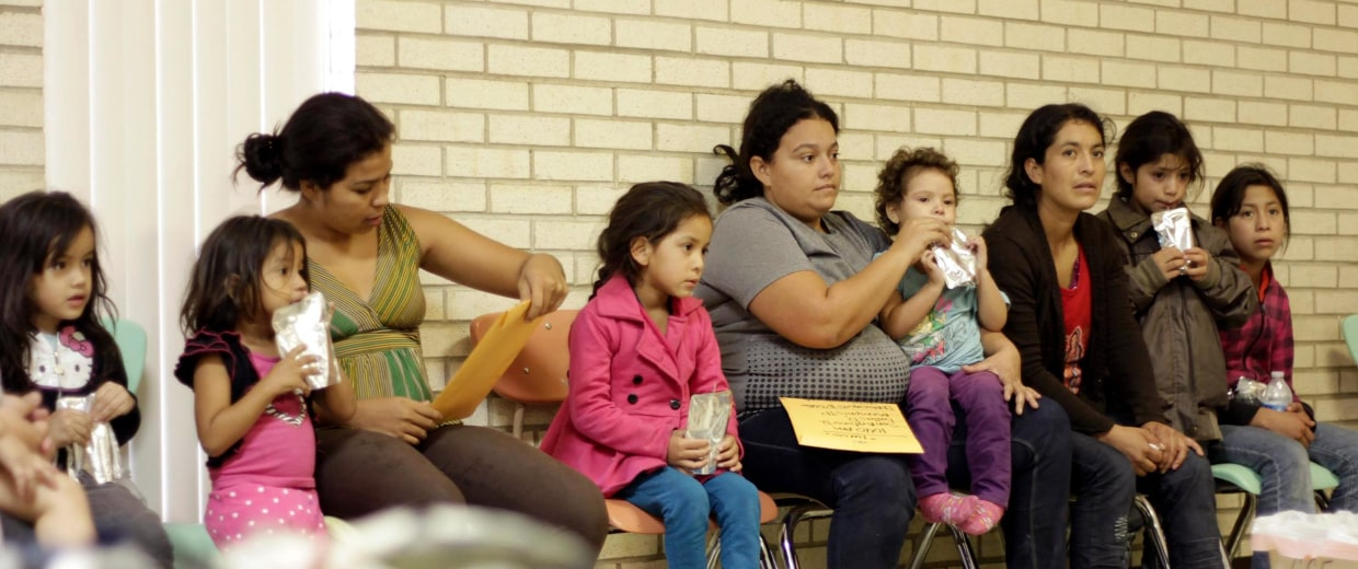 Image: Migrants sit at the Sacred Heart Catholic Church temporary migrant shelter in McAllen, Texas
