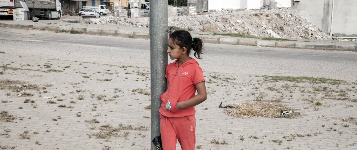 Image: Najua, 9, waits for the bus on her first day of school.