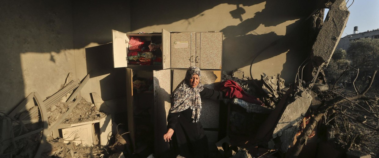Image: Palestinian woman inspects her house which police said was damaged in an Israeli air strike on a neighbourin