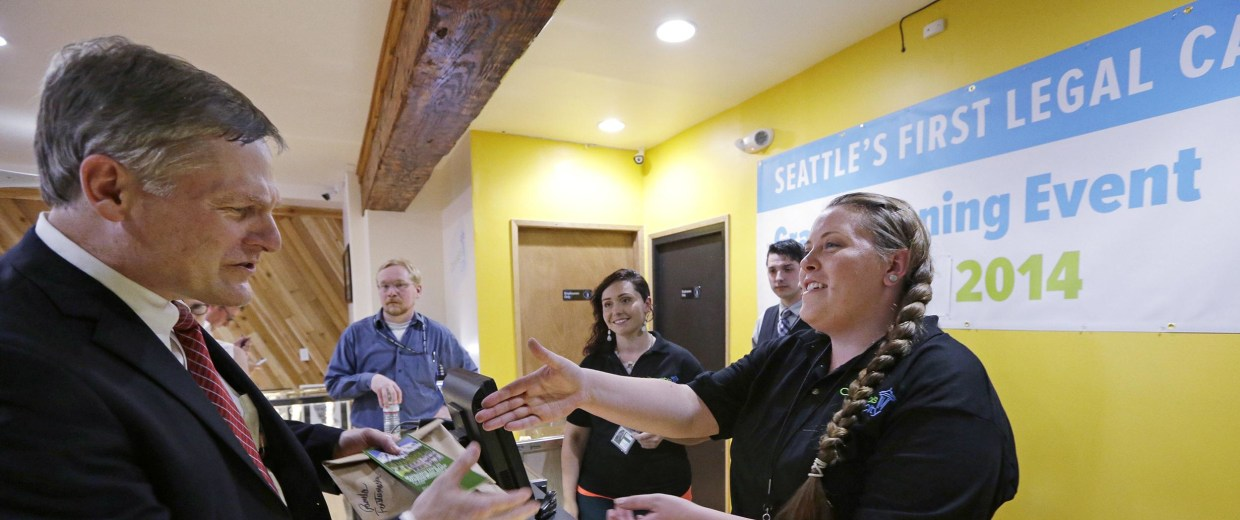 Image:Seattle City Attorney Pete Holmes, left, shakes hands with clerk Pam Fenstermacher after purchasing marijuana at Cannabis City in Seattle.