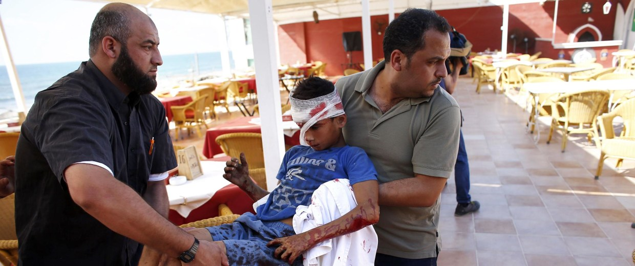 Image: Palestinian employees of Gaza City's al-Deira hotel carry a wounded boy