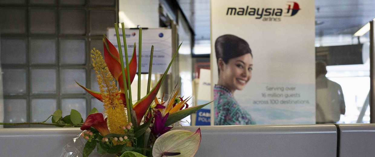 A bouquet of flowers is placed on a Malaysia Airlines counter at Schiphol Airport