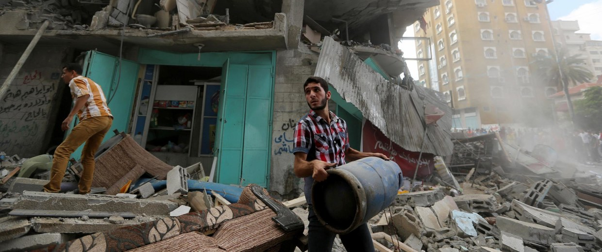 Image: A Palestinian carries a gas cylinder as he and others salvage from the rubble of their destroyed homes in an apartment building after it was hit by an Israeli missile strike in Gaza City, Friday, July 18, 2014