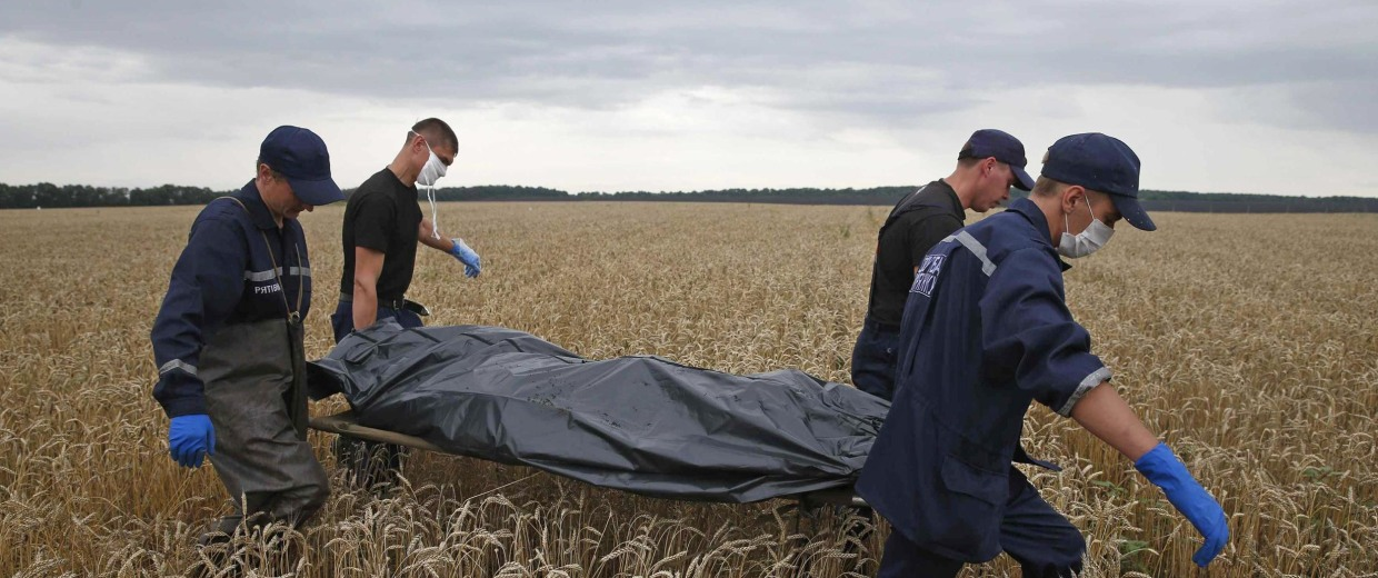 Image: Members of the Ukrainian Emergency Ministry carry a body at the crash site of Malaysia Airlines Flight MH17, near the settlement of Grabovo