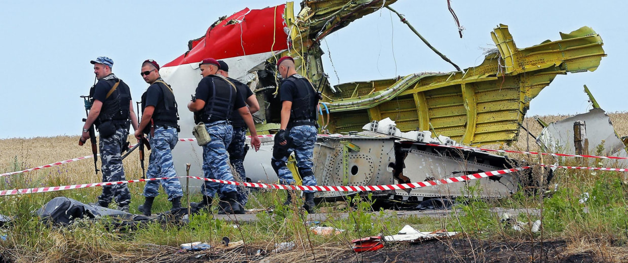 Image: Rebel soldiers pass a big piece of debris at the main crash site of the Boeing 777 Malaysia Airlines flight MH17