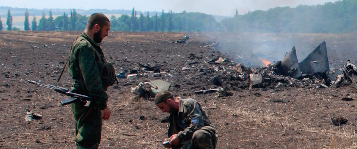 Image: In this frame grab, pro-Russians collect parts of the burning debris of a Ukrainian military fighter jet, shot down at Savur Mogila, eastern Ukraine