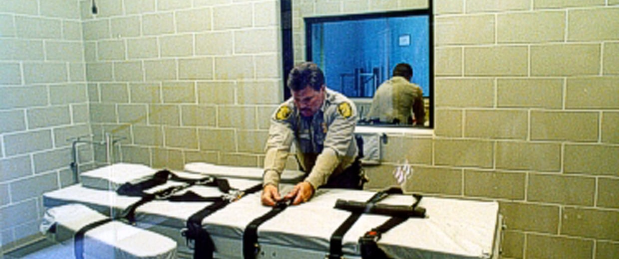 Image: An unidentified Arizona Corrections Officer adjusts the straps on the gurney used for lethal injections
